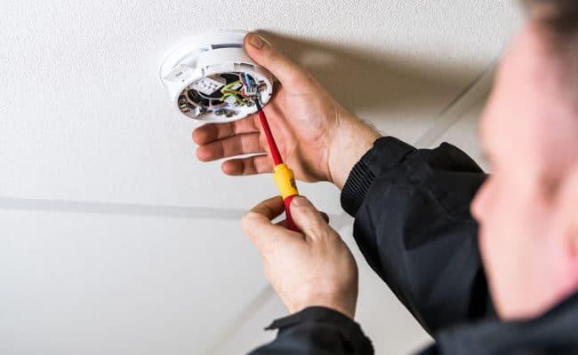 Engineer maintaining fire alarm